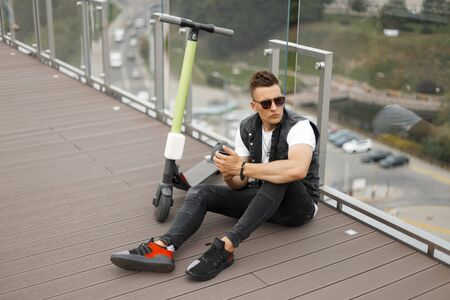 Handsome young man model in sunglasses in a trendy denim vest in jeans in sneakers with a phone sit on a wooden floor next to an electric scooter. Stylish hipster guy is resting near a glass wall. Foto de archivo - 129904286
