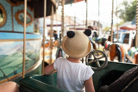 View from the back on a little girl in a stylish white T-shirt in a beautiful straw hat with ears. Baby sit on a carousel in an amusement park. Family vacation in Europe.