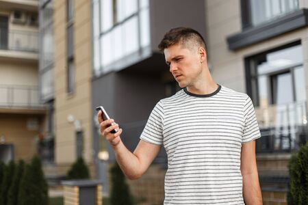 Young handsome man manager in a fashionable striped t-shirt with a stylish hairstyle stands with a mobile phone in hands next to a modern building in the city. Business guy outdoors. Modern technology