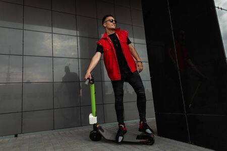 Stylish young man hipster in a trendy red vest in sunglasses in black jeans stands next to a vintage scooter near a black building in the city. Attractive guy resting after riding a scooter. Menswear. Banco de Imagens
