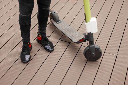 Male legs in gray jeans in trendy black sneakers next to an electric scooter on a summer day. Fashionable guy stands on a wooden floor near a modern scooter. Close-up.