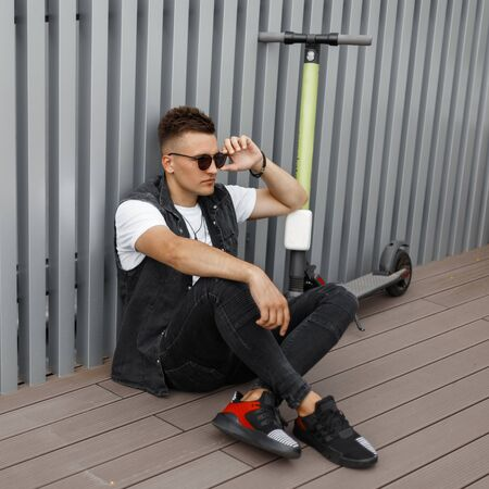 Model of a young hipster man in sunglasses in stylish jeans clothes with a scooter is sitting on the terrace near the metal wall. Guy is sitting on the floor next to an electric scooter. Relaxation. Banco de Imagens