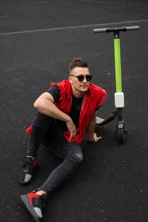 Handsome young man in sunglasses in a stylish red denim vest in black vintage jeans in sneakers sitting on the pavement next to an electric scooter. Attractive hipster guy relaxes outdoors. Leisure.