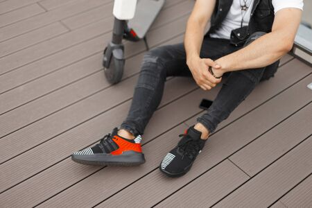 Young stylish man in trendy gray denim clothes in sneakers sits on a wooden floor next to a modern scooter. Urban guy relaxes in the outdoors. Closeup scooter and male body.