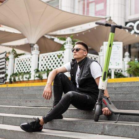Attractive young man hipster in trendy black jeans clothes in sunglasses sits next to an electric scooter on vintage stone steps near a summer cafe.Handsome guy enjoys relaxing after riding a scooter. Banco de Imagens