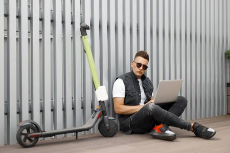 Attractive young man hipster in stylish jeans clothes in sunglasses in sneakers works on the Internet on a laptop. Trendy handsome guy is resting after riding an electric scooter near metallic wall.