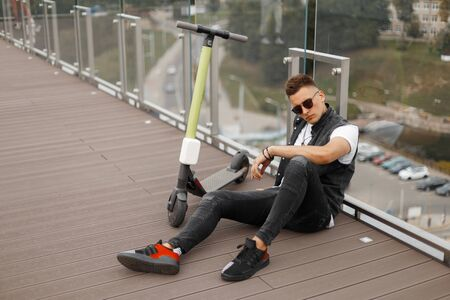 Young urban guy in fashionable gray jeans clothes in trendy black sunglasses sits next to an electric scooter on a wooden floor near a glass wall. Attractive guy enjoys relaxes after riding a scooter. Banco de Imagens