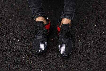 Top view on male legs in trendy sneakers on a black background. Young stylish man in jeans in sports fashionable red-black shoes. New seasonal collection of fashionable men's sneakers. Stock Photo