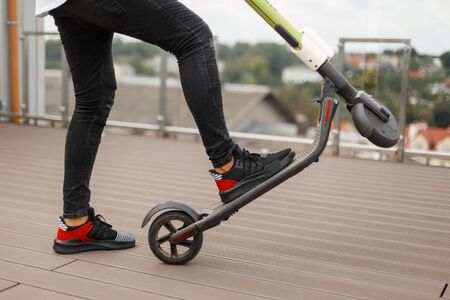 Young man in gray jeans in sneakers posing with an electric scooter on a summer terrace. Closeup of male legs on a modern scooter on a city background. Leisure.