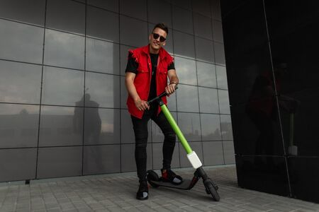Joyful young hipster man in stylish red-black jeans clothes in sports sneakers in sunglasses with a vintage scooter stands near a modern building in the city. Fashionable guy walks on the street. Foto de archivo - 129904542