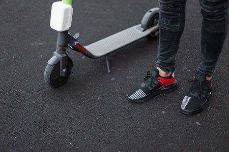 Legs of a trendy young man in stylish black jeans in a shoes stand next to an electric scooter on asphalt. Fashionable guy is resting after riding modern scooter outdoors. Close-up. Active lifestyle.