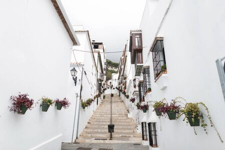 Historic street in the old white city with a vintage staircase and with colorful flower pots. Andalusia. Malaga. Southern Spain. Stock Photo