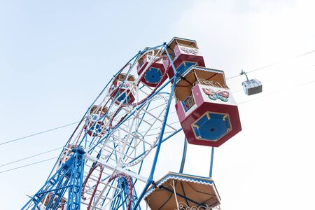 Giant ferris wheel with colorful empty booths. Bottom view of a ferris wheel and blue sky on a sunny summer day. Stock Photo
