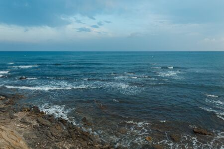 Restless sea with waves with rocks with a blue sky with clouds. Ocean horizon. Beautiful seascape.
