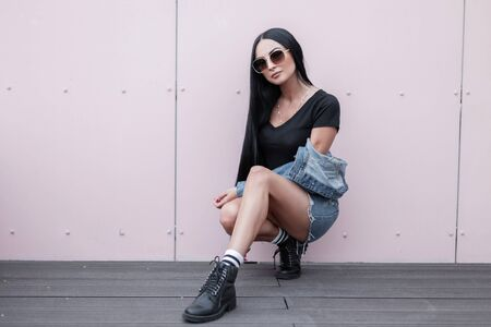 Pretty young hipster woman in sunglasses in a fashionable blue denim clothes in stylish leather black autumn boots sitting near a wall on the street. Sexy urban girl relaxes outdoors. Street fashion.