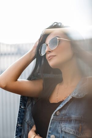 Portrait of an attractive pretty young woman with chic black hair in stylish clothes in sunglasses in an autumn bright sunny day. Beautiful sexy girl fashion model enjoying the suns rays outdoors.