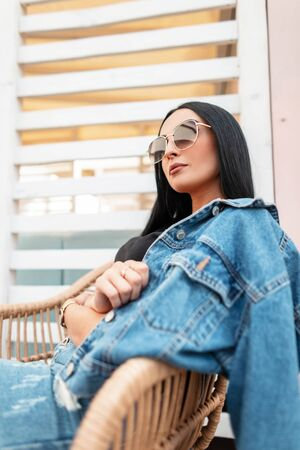 Pretty sexy young hipster woman in trendy sunglasses in a T-shirt in a vintage denim jacket in a blue skirt rest on a straw chair outdoors in a cafe on a summer day. Attractive brunette girl model.