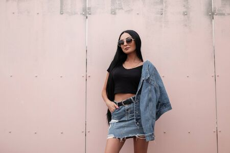 Pretty beautiful young hipster woman in a stylish denim jacket in a trendy black top in a vintage jeans skirt in sunglasses stands near a wall in the city. Attractive brunette girl with long hair. Foto de archivo