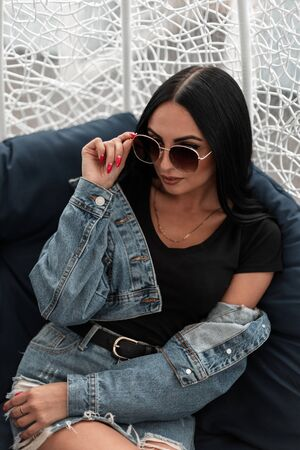 Attractive young woman model straightens stylish sunglasses sitting on a soft chair on the terrace of a summer cafe. Pretty beautiful hipster girl in trendy jeans clothes rest outdoors in the city. Foto de archivo