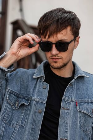 Stylish young man hipster straightens fashionable sunglasses. Portrait of a handsome guy in a trendy blue denim jacket in a black t-shirt outdoors in the city. American style. Foto de archivo - 132745051
