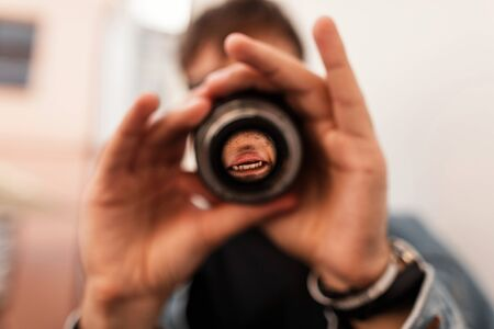 Young professional male photographer is looking into a modern lens a camera. Men's hands hold a lens close-up. Creative photo Banque d'images - 132556852