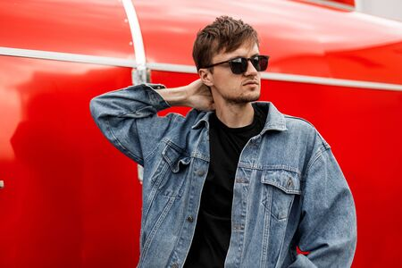 Fashionable young man hipster posing near modern metal red wall. Handsome guy model in trendy denim clothes in stylish sunglasses enjoys a vacation in the city on a spring day. American street style. Foto de archivo - 132712690
