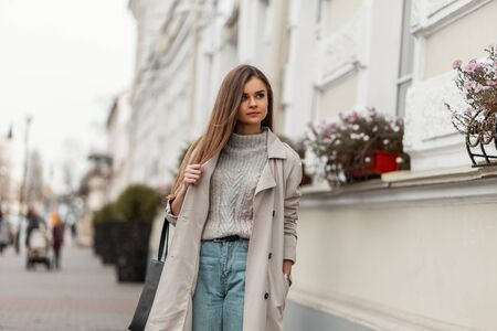Modern cute young woman in a vintage sweater in a fashionable trench coat in jeans with a black leather bag standing on a street in the city on a warm autumn day.