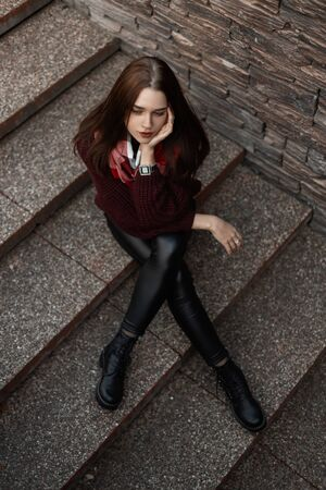 Modern young in a boots in a fashionable knitted vintage sweater in leather pants with a plaid scarf is sitting in the city on a stone staircase. Stockfoto