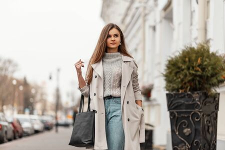 Pretty trendy young woman in a stylish trench coat in a vintage knitted sweater in blue jeans with a leather bag enjoys a walk along the street.