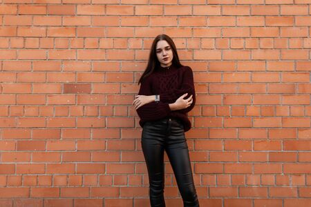 European pretty young fashionable woman in a stylish knitted burgundy sweater in trendy black leather pants stands in the city near a brick wall.