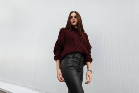 Attractive young woman in a fashionable knitted sweater in stylish leather black pants poses near a modern white wall in the city. Imagens