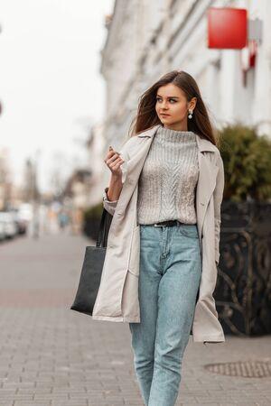 Modemodell einer jungen Frau in einem Vintage-Trenchcoat in einem stilvollen Strickpullover mit einer schwarzen Ledertasche geht durch die Stadt in der Nähe eines weißen Gebäudes.