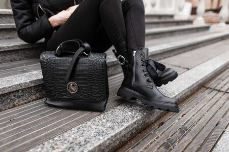 Young stylish woman in fashionable autumn black clothes sits on the steps in the city. Close-up of female legs in jeans in boots with a leather fashion handbag. Trendy women's shoes and accessories.