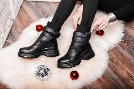Young woman in a room on a white fluffy carpet among New Years toys sits and measures leather fashionable black boots. Close-up of female legs in stylish winter shoes. Holiday shopping. Reklamní fotografie