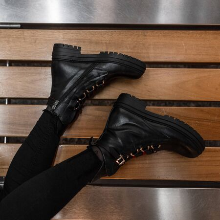 Fashionable leather brutal black boots on a wooden bench. Top view on female legs in trendy black jeans in youth winter stylish shoes. Close-up womens seasonal footwear.