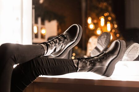 Closeup female legs in black jeans in fashionable black leather winter boots near a vintage mirror with bright light bulbs indoors. Girl chooses shoes for a party. Casual youth modern style. Reklamní fotografie