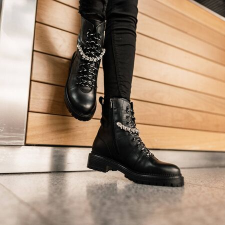 Female legs in fashionable leather black autumn boots in vintage black jeans. Trendy girl is standing in the store near wooden wall. Stylish youth casual outfit. Details of everyday look. Close-up.