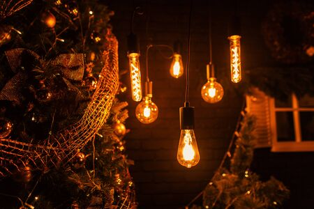 Cozy room with a Christmas tree with golden garlands with vintage lamps with mirror balls with yellow light in the evening time. Merry Christmas and Happy New Year. Close-up. 免版税图像