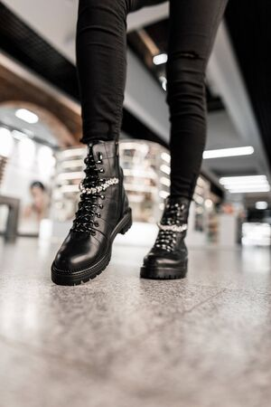Close-up of female legs in black trendy jeans in leather black stylish lace-up boots. Fashionable woman poses on the shop mall. Autumn fashion womens shoes with shiny rhinestones.