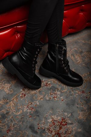 Closeup of female legs in fashionable leather black boots with lacing in vintage jeans indoors. Stylish young woman in trendy shoes sits on a red chic sofa in a store. Autumn-spring casual style.