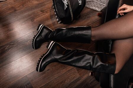 Top view on female legs in stylish leather boots and on a black fashionable backpack with a skull pattern. Young woman sits on a sofa in a shoe and accessories store. Youth collection of stylish shoes Reklamní fotografie