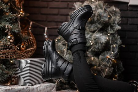 Stylish black leather winter boots on female legs near a beautiful festive Christmas tree with vintage toys in the studio. Christmas sale. Fashionable winter womens shoes. Close-up.
