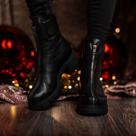 Fashionable leather black womens winter boots. Young woman in jeans in stylish shoes stands in a room near the holiday mirror balls. New Years shopping. New seasonal shoe collection.