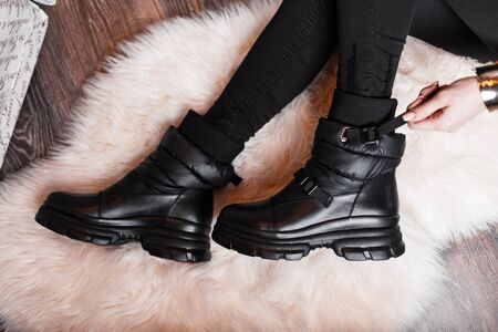 Top view on the legs of a young woman in fashionable leather shoes in stylish black jeans in the studio. Trendy modern youth new collection of seasonal boots. Seasonal footwear. Casual fashion.