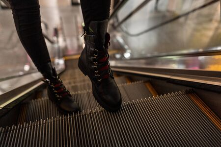 Young stylish woman in fashionable leather black boots with red shoelaces in vintage jeans on the escalator is a. Modern girl in trendy shoes is walking around the store. Closeup of female legs.
