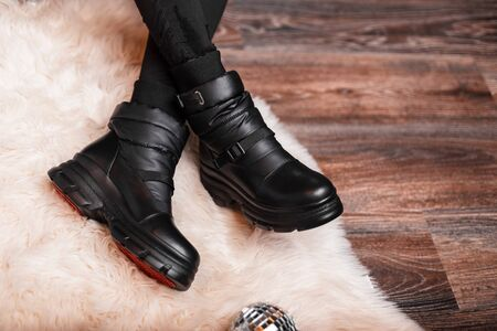 Fashionable women's black warm winter boots on female legs. Close-up. Youth stylish autumn-winter collection of leather warm shoes.