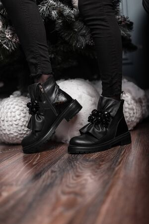 Youth fashionable leather black womens winter boots. Stylish young woman in jeans in trendy shoes stands in a room near beautiful white Christmas balls. New seasonal shoe collection.