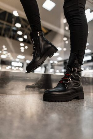 Young woman in a fashionable black leather boots with red shoelaces in vintage jeans poses in a store. Close up of female legs in stylish seasonal shoes. Autumn-winter footwear. New collection.