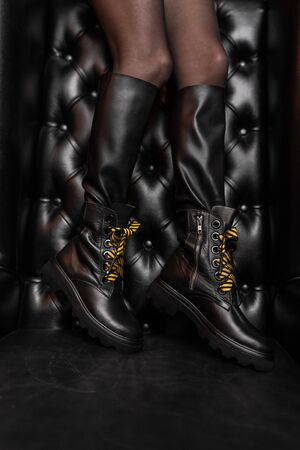 Autumn stylish black boots on female legs. Modern young trendy girl in fashionable shoes is standing in a store near a black leather wall. Fashion and Style. Close-up. Reklamní fotografie