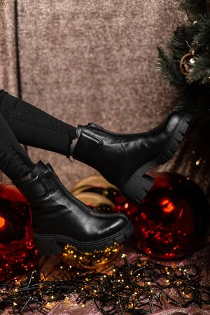 Closeup of stylish black winter boots on female legs indoors. Young woman in fashionable leather shoes in black jeans poses near beautiful holidays balls in a New Years studio.